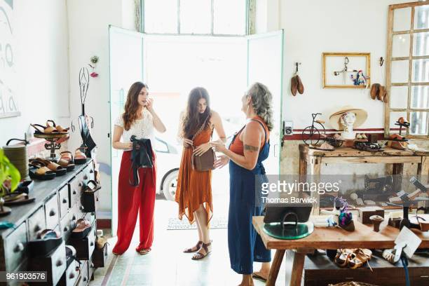 shop owner helping two friends shopping in handmade leather goods store - red pants stock pictures, royalty-free photos & images