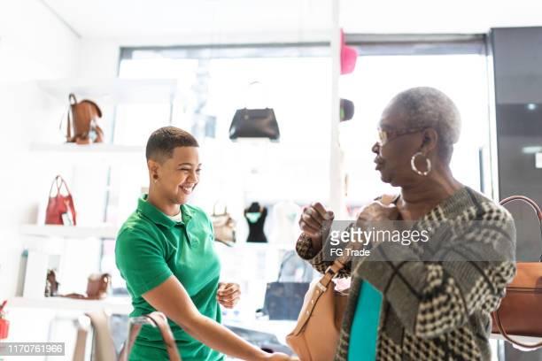 propriétaire de magasin aidant la femme choisissant un sac à main, affichant des options - sac à main noir photos et images de collection