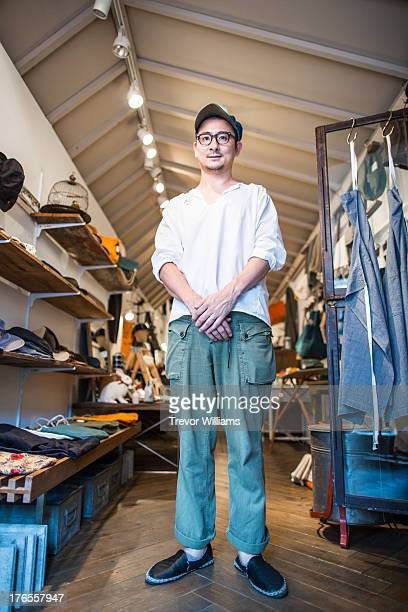 A shop owner in his thirties standing in his shop