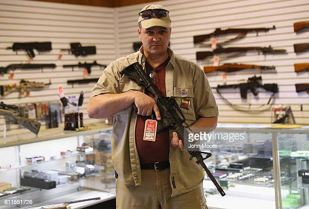 Shop owner Jeff Binkley displays an AR15 'Sport' rifle at Sarge's Sidearms on September 29 2016 near Benson Arizona He said he redesigned and renamed...