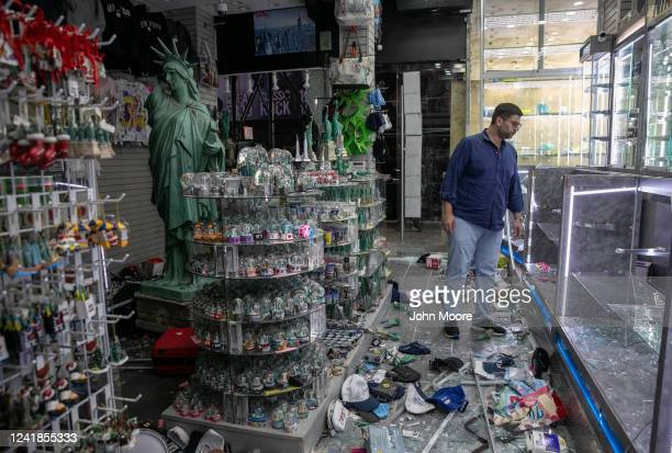 A shop owner looks over damage in a looted souvenir and electronics shop near Times Square after a night of protests and vandalism over the death of...