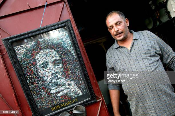 Shop owner of Creations Pneumatiques next to picture of Bob Marley.