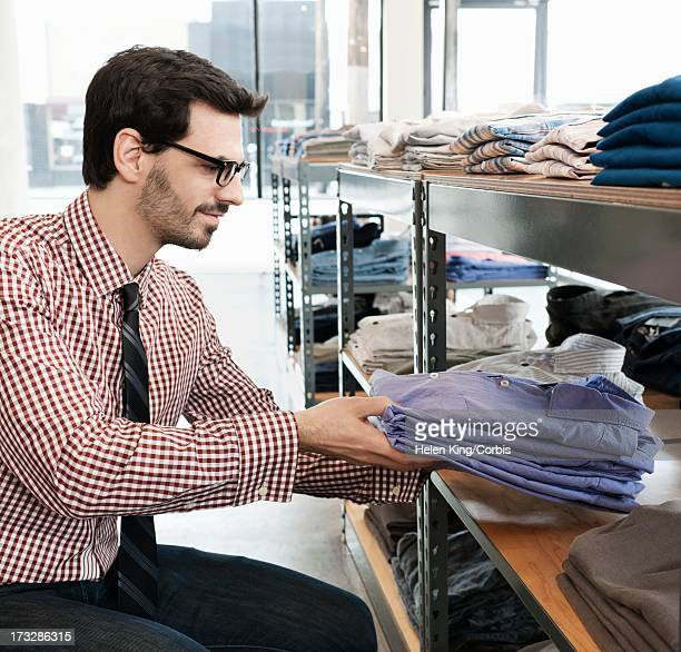 shop owner organizing shirts in clothing store - menswear ストックフォトと画像