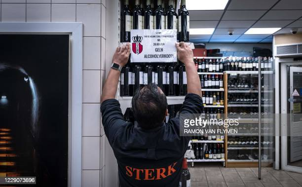 A shop owner places a sign reading Alcohol sales forbidden after 8pm at a night shop in Amsterdam on October 14 2020 The Netherlands will go into...