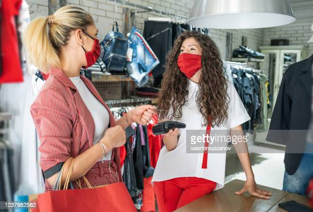 shop owner receives wireless contactless payment from a customer who is shopping in the mall after reopening stores after covid-19 - reopening stock pictures, royalty-free photos & images