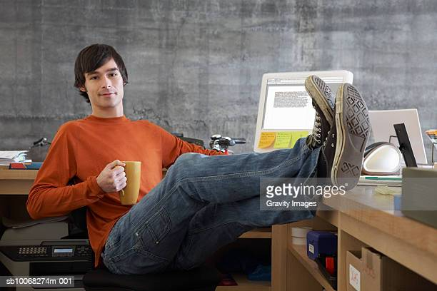 shop owner relaxing at desk holding mug, feet up, portrait - feet up stock pictures, royalty-free photos & images