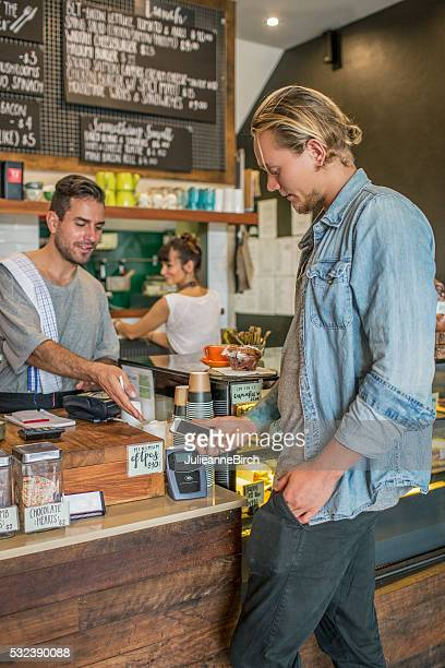 Shop owner showing contactless payment machine