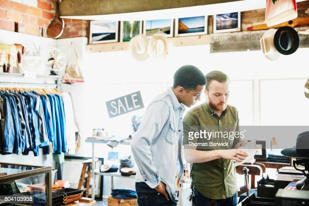 Shop owner showing journal to man shopping in mens boutique