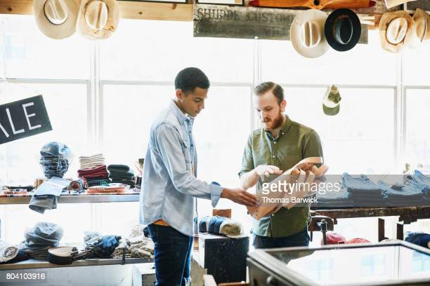 Shop owner showing leather bag to customer in mens boutique