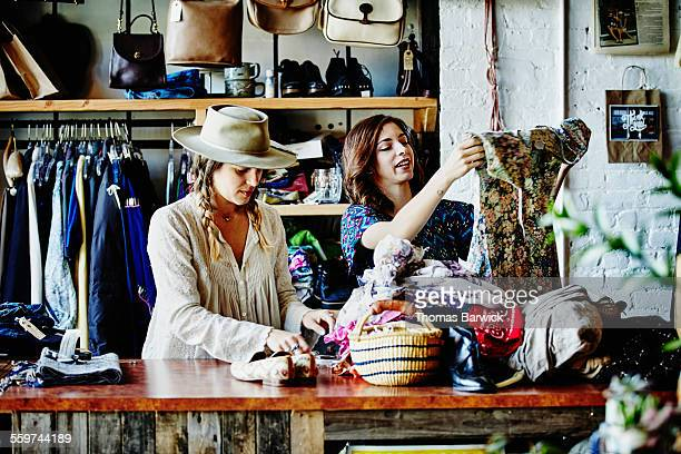 Shop owner sorting through clothing with coworker