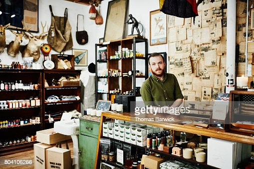 Shop owner standing behind counter in mens boutique