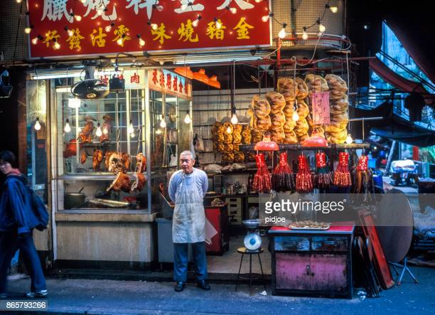 shop owner standing in front of poultry shop on Temple Street night market in Kowloon Hong Kong China