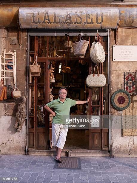 shop owner stands outside his shop - palma majorca stock photos and pictures
