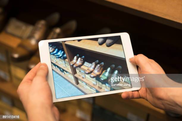 Shop owner taking photo of leather shoes in men's boutique