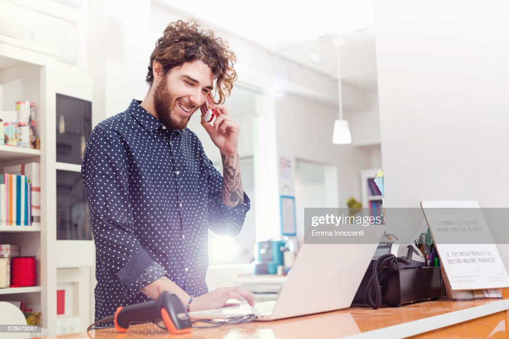 shop owner using laptop and talking on cellphone : Stock Photo