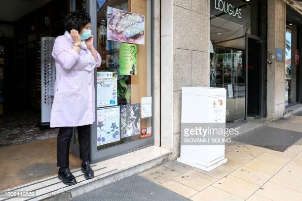 A shop owner wearing a respiratory mask as part of precautionary measures against the spread of the new COVID19 coronavirus stand by her shop in...