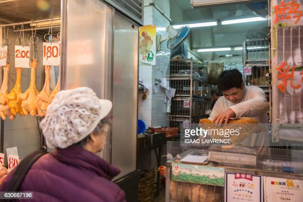 A shop owner weighs a live chicken for a customer in the Wanchai markets of Hong Kong on December 30 2016 Hong Kong on Friday confirmed its second...