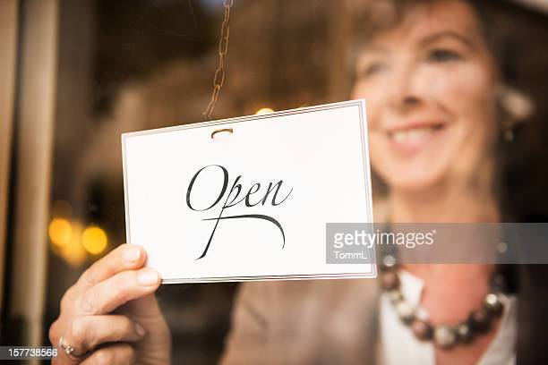 Shop Owner with OPEN Sign