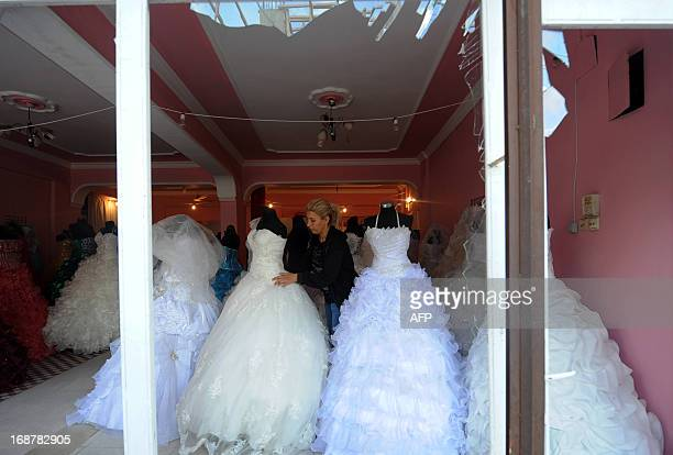 A shop owner works at fixing wedding gowns on May 15 2013 following May 11 twin blasts at the Turkish town of Reyhanli in Hatay just a few kilometres...