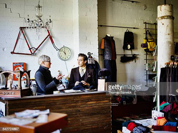 shop owners behind counter in boutique - leanintogether stock pictures, royalty-free photos & images