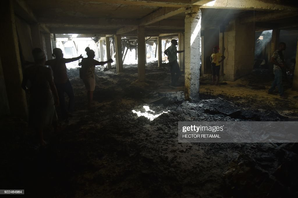 Shop owners inspect their destroyed shops in the worse-hit area at the Nan Gerit Market in Port-au-Prince on February 21, 2018. A fire gutted the textiles market in Haiti's capital on February 18. /