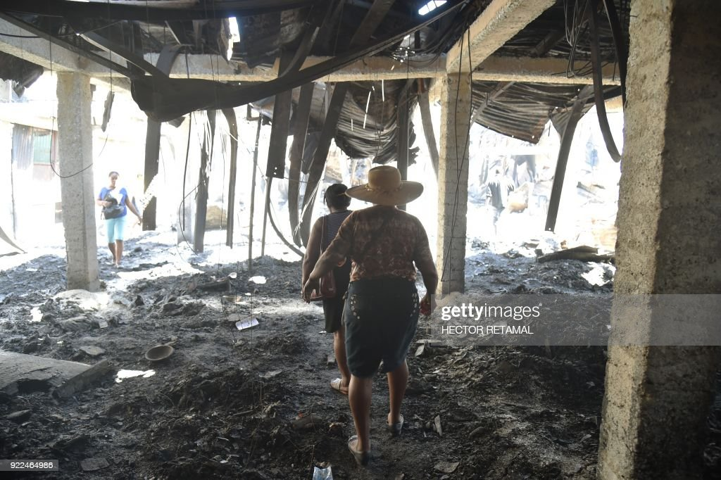 Shop owners inspect their destroyed shops in the worse-hit area at the Nan Gerit Market in Port-au-Prince on February 21, 2018