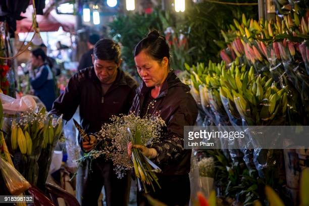 Shop owners prepare their flowers at Quang Ba flower market a favorite shopping place for local people for the Lunar New Year on February 14 2018 in...