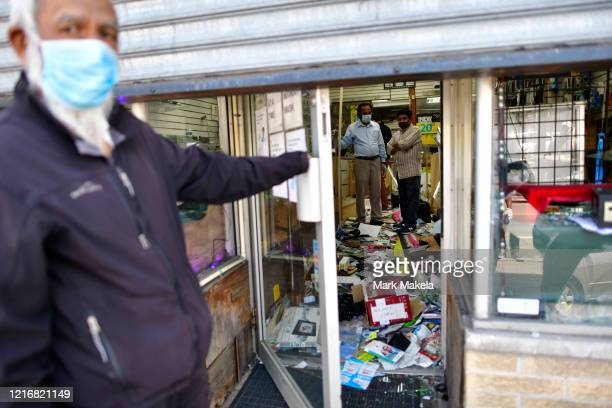 Shop owners survey the damage to their store in the aftermath of widespread unrest following the death of George Floyd on June 1 2020 in Philadelphia...
