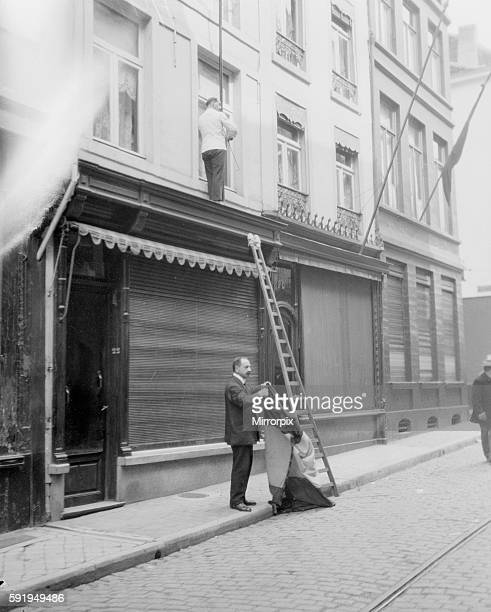Shop owners taking down the Belgium flags before Louvain is occupied by the advancing German army August 21st 1914