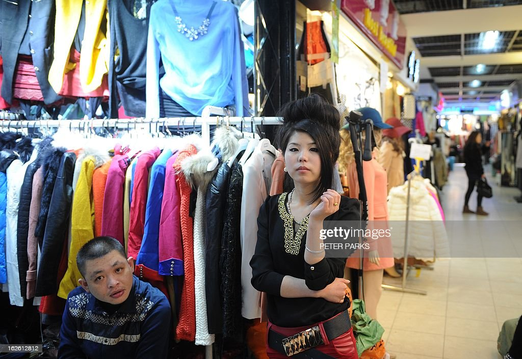 Shop owners wait for customers in a wholesale clothing market in Shanghai on February 25, 2013. China's manufacturing growth hit a four-month low in February but remained positive, British banking giant HSBC said on February 25, noting that the world's second-biggest economy was still recovering slowly. AFP PHOTO/Peter PARKS