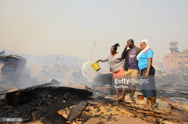 Shop owners with detergent water trying to put out a fire that broke out at the popular timber market in Mushin, Lagos January 25, 2020. There have...