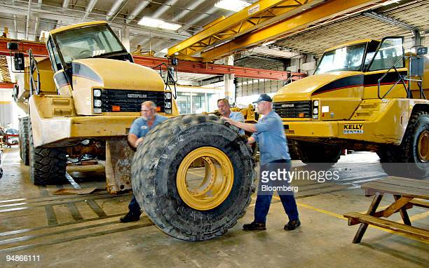 Shop technicians wheel a tire/wheel assembly past a pair of Caterpillar Articulated Dump Trucks, Thursday, February 2 at Kelly Tractor in West Palm...
