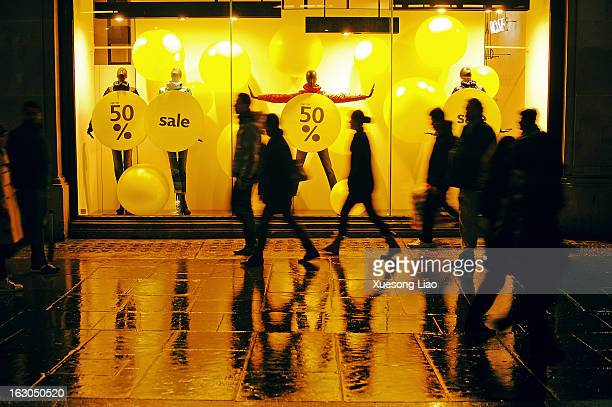 Shop window,People walking,Wet ground,Reflection,Street people silhouette,London Street,Shopping,Retail,People moving image,High street,Night.Warm...