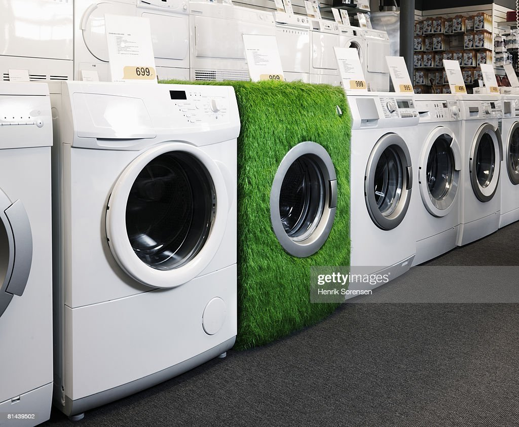 Shop with washers lined up on display and one washer covered with grass. : Stock Photo