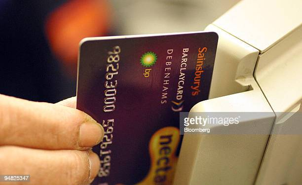 A shop worker credits loyalty points to a customers card at the Sainsbury supermarket in Cromwell Road London Wednesday April 7 2004