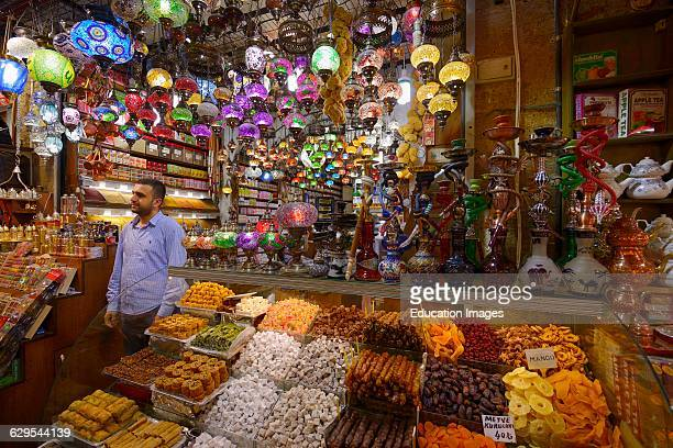 Shop worker in the Egyptian Spice Bazaar Istanbul with Turkish Delight water pipes and lamps
