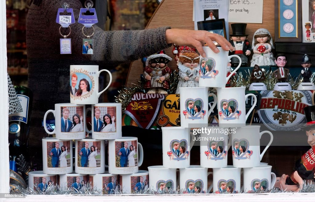 A shop worker makes adjustments to memorabilia celebrating the engagement of Britain's Prince Harry to fiancée US actress Meghan Markle in a gift shop in Windsor, west of London on December 8, 2017. Britain's Prince Harry will marry his US actress girlfriend Meghan Markle in Windsor, 25 miles west of London in May 2018. / AFP PHOTO / Justin TALLIS