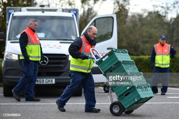 Shop worker moves trays used in the click and collect service at a Tesco supermarket in Pembury, south-east of London on November 6 as the second...