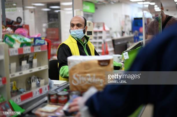 Shop worker wearing a protective face covering to combat the spread of the coronavirus, serves customers at an Asda supermarket in London on December...