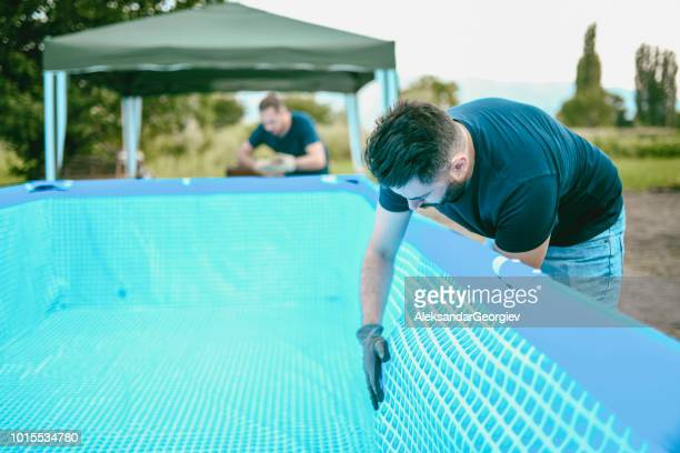 Shop Workers Setting Up Swimming Pool
