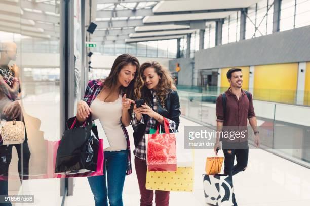 viciados em compras desfrutando de vendas sazonais - apontando sinal manual - fotografias e filmes do acervo