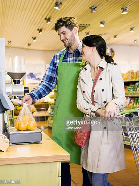 shopassistant weighing oranges for female customer