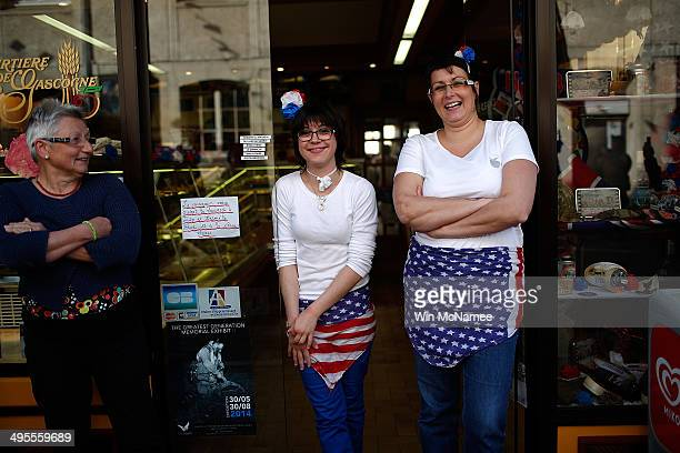 A shopkeeper and her daughter wear American flags as aprons as they watch a military parade marking the week of DDay June 4 2014 in Carentan France...