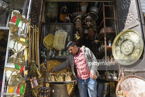Shopkeeper arranges a display of locally-crafted lanterns and othe items as people shop ahead of the Muslim holy month of Ramadan, at a workshop in...