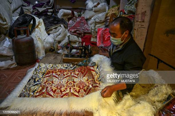 Shopkeeper arranges a piece of cloth inside a shop at a market in Leh, the joint capital of the union territory of Ladakh, on June 27, 2020.