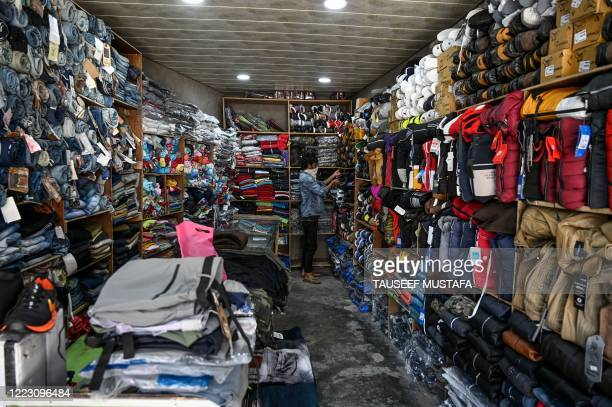 Shopkeeper arranges clothes inside a shop selling Chinese items at a market in Leh, the joint capital of the union territory of Ladakh, on June 27,...