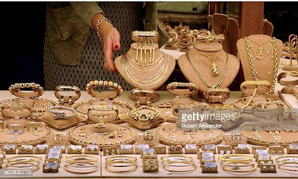 A shopkeeper arranges jewelry in the window of her shop on the landmark Ponte Vecchio bridge in Florence Italy Gold jewelry merchants have operated...