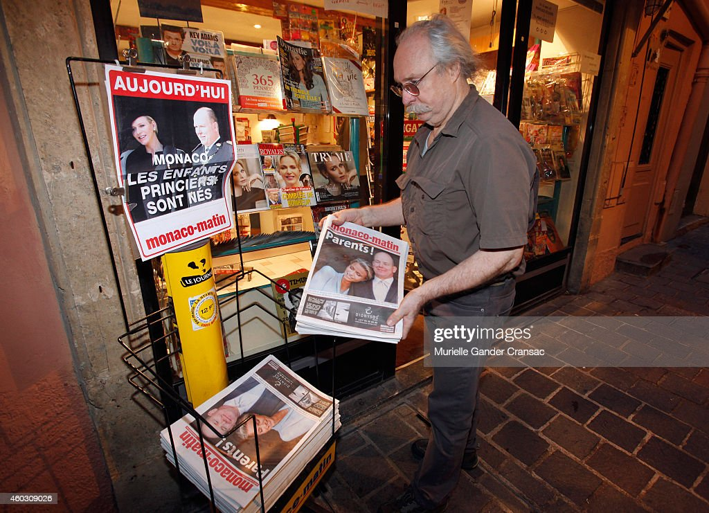 A shopkeeper arranges newspapers with displaying the front page story of the birth of the royal twins Prince Jacques and Princess Gabriella outside the Monaco Palace on December 11, 2014 in Monaco, Monaco.