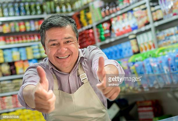Shopkeeper at a local food shop with thumbs up