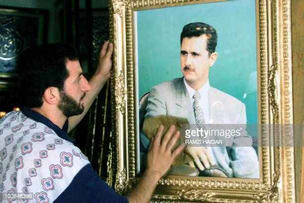 A shopkeeper cleans a portrait of Syrian heir apparent Bashar alAssad in Damascus 20 June 2000 as the ruling Baath party prepared to wind up its...